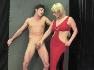 Blondă Seducatoare Într-O Rochie Roșie Sexy Place Un Cocoș Mare Cu Mâinile